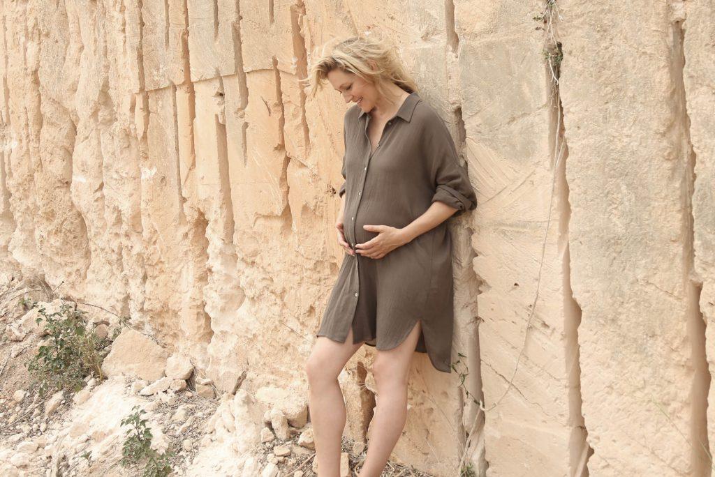 Model Christine lehnt an einer hellbeigen Steinbruchwand. Sie trägt ein schlammfarbenes, knieumspielendes Hemd, hält sich liebevoll den Bauch mit einem lächelnden Blick nach unten.